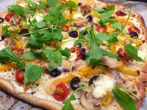 Pizza met crème fraîche, tomaat, champignons, rucola, mozzarella